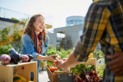 Azienda agricola, ragazza che vende frutta e verdura al banco